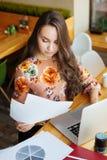 Frau, die das Papier betrachtet und auf Laptop schreibt stockbilder