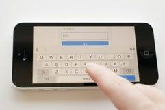 Frau, die das Passwort für gmail Kontoanmeldung auf iphone 5c schreibt Lizenzfreie Stockbilder