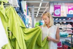 Frau, die das rechte Tuch für ihre Wohnung in einem modernen Hausausstattungsspeicher wählt Stockfoto