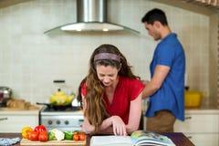 Frau, die das Rezeptbuch und -mann kochen auf Ofen überprüft Stockbild