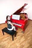 Frau, die das rote großartige Klavier spielt Lizenzfreie Stockbilder