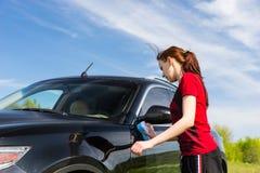 Frau, die das rote Hemd wäscht schwarzes Auto auf dem Gebiet trägt Lizenzfreie Stockfotos