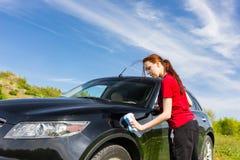 Frau, die das rote Hemd wäscht schwarzes Auto auf dem Gebiet trägt Lizenzfreie Stockbilder