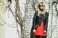 Frau, die das rote Kleid aufwirft in der Stadt trägt Stockfoto