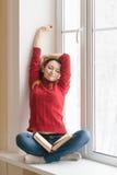 Frau, die das Sitzen auf einem Fensterbrett mit einem Buch ausdehnt Stockfoto
