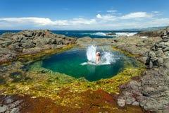 Frau, die das Spritzen springt in schönes Felsenpool macht stockbilder