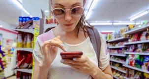 Frau, die das Telefon im Speicher verwendet stock footage