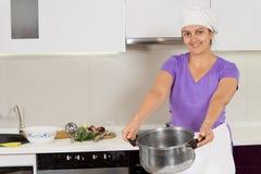 Frau, die das Topflächeln kochend trägt lizenzfreie stockfotografie