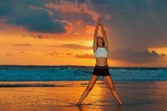 Frau, die das Trainieren auf Sonnenuntergangstrand tut Stockfotos