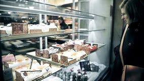 Frau, die das Wählen für besten Kuchen im Bäckerspeicher bewundert stock video