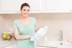 Frau, die das Waschen oben in der Küche tut Stockfoto