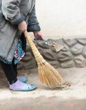 Frau, die das Yard mit einem Besen fegt Lizenzfreie Stockbilder