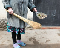 Frau, die das Yard mit einem Besen fegt Lizenzfreies Stockfoto