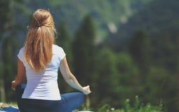Frau, die das Yoga meditiert im Lotussitz mit seinem zurück tut Stockbilder