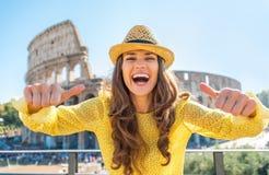 Frau, die Daumen oben vor colosseum zeigt Lizenzfreies Stockfoto