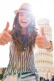 Frau, die Daumen oben vor Turm von Pisa zeigt Lizenzfreies Stockfoto