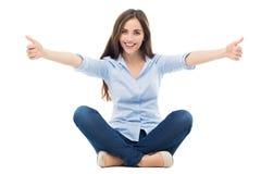 Frau, die Daumen sitzt und sich zeigt Lizenzfreie Stockfotos