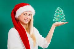 Frau, die dekorativen Weihnachtsbaum hält Lizenzfreies Stockfoto