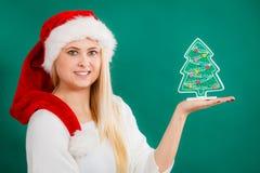 Frau, die dekorativen Weihnachtsbaum hält Stockfotografie