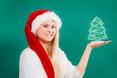 Frau, die dekorativen Weihnachtsbaum hält Stockfoto