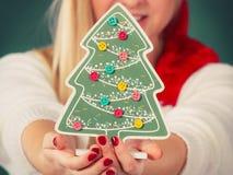 Frau, die dekorativen Weihnachtsbaum hält Stockfotos