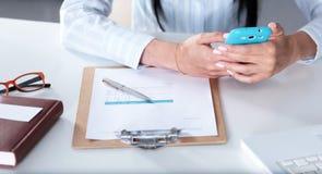 Frau, die an dem celphone, sitzend am Schreibtisch arbeitet Lizenzfreie Stockfotos