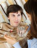 Frau, die dem Ehemann medizinischen Sirup gibt Stockfoto