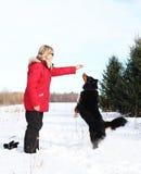 Frau, die dem Hund Festlichkeiten gibt Stockfoto
