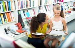 Frau, die dem kleinen Mädchen offenes Buch zeigt lizenzfreies stockbild