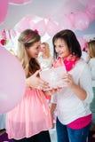 Frau, die dem schwangeren Freund auf Babyparty Geschenk gibt Stockfotografie