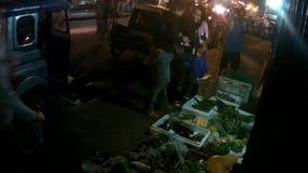 Frau, die dem Straßennachtumwelt, -c$drängen und -verschmutzung, ein mageres Leben zu erwerben verkauft Gemüse trotzt stock video footage