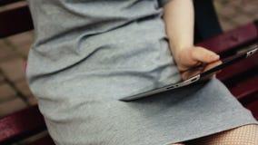 Frau, die an dem Tablet-Computer draußen sitzt auf Bank arbeitet Abschluss oben stock footage