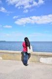 Frau, die in den Abstand Meer betrachtet Stockfotografie