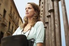 Frau, die den Aktenkoffer sich lehnt am Geländer hält Stockbilder