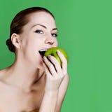 Frau, die den Apfel lächelt auf grünem Hintergrund isst. stockfotografie