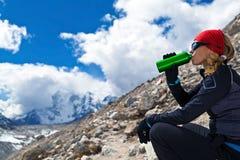 Frau, die in den Bergen trinkt Stockfotos