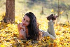 Frau, die in den Blättern erwägt Lizenzfreie Stockbilder
