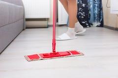 Frau, die den Boden in einem Wohnzimmer wischt Lizenzfreie Stockfotografie
