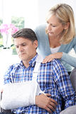 Frau, die den Ehemann leidet mit Arm-Verletzung tröstet lizenzfreie stockfotografie