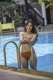 Frau, die den eleganten Bikini aufwirft neben Swimmingpool trägt stockfoto