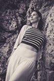 Frau, die an den Felsen sich lehnt Stockbild