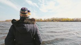 Frau, die den Fluss während eines kalten Frühlings-Tages betrachtet stockfotografie