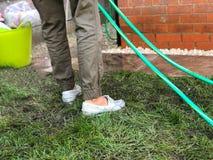 Frau, die den Gartenschlauch verwendet, um Platten in ihrem hinteren Garten zu säubern lizenzfreie stockbilder