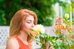 Frau, die den Geruch von blühenden Rosen genießt stockfoto