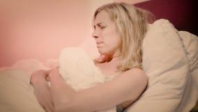 Frau, die in den glaubenden Schmerz des Betts in ihrem Bauch liegt und es reibt stock video