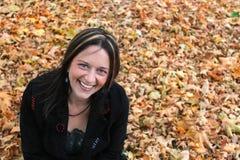 Frau, die in den Herbstblättern sitzt Stockbilder