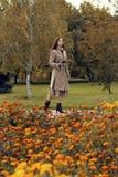 Frau, die in den Herbstpark mit Regenschirm geht Lizenzfreie Stockbilder