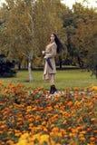 Frau, die in den Herbstpark mit Regenschirm geht Lizenzfreies Stockbild