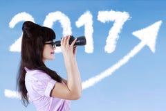 Frau, die den Himmel mit einem Teleskop betrachtet Lizenzfreies Stockfoto