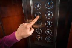 Frau, die den Knopf im Aufzugsinnenraum bedrängt lizenzfreie stockbilder